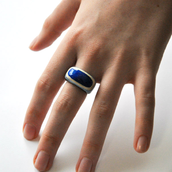 layered paper ring with bright blue accent on hand model